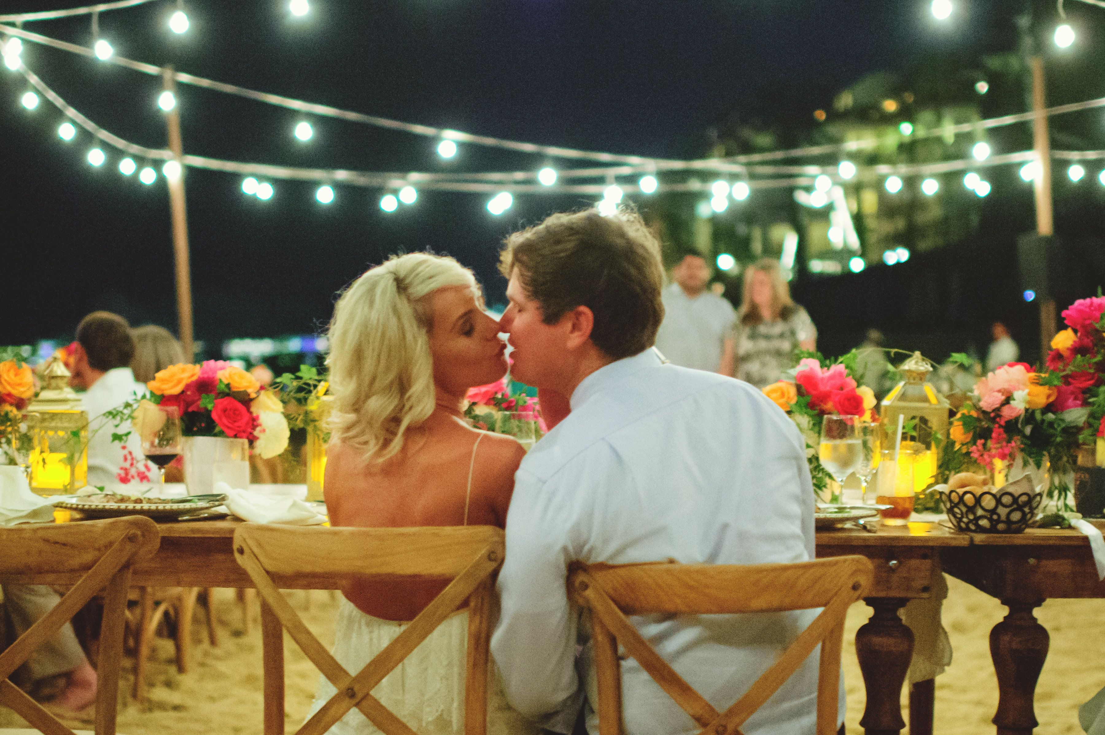 bride and groom kissing at wedding reception. Design by Cabo Wedding Services