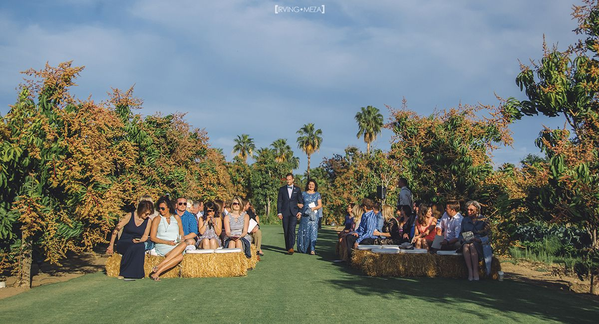 Wedding Ceremony at Wedding Venue Flora Farms in Cabo San Lucas, Mexico. The Groom is walking down the aisle with his mother