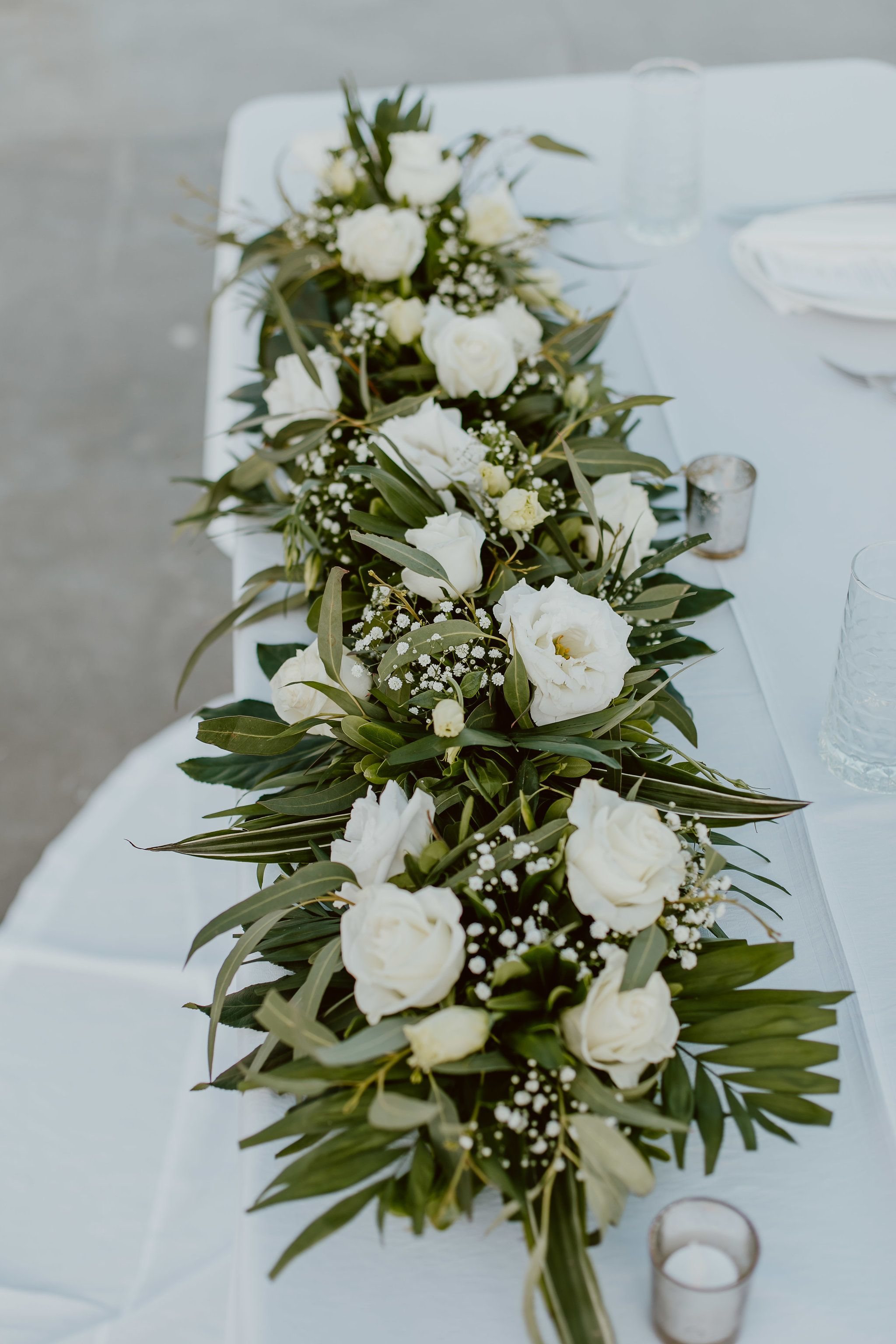 Table Centerpieces with greenery with White Flowers on Sweetheart Table at The Cape in Los Cabos Mexico