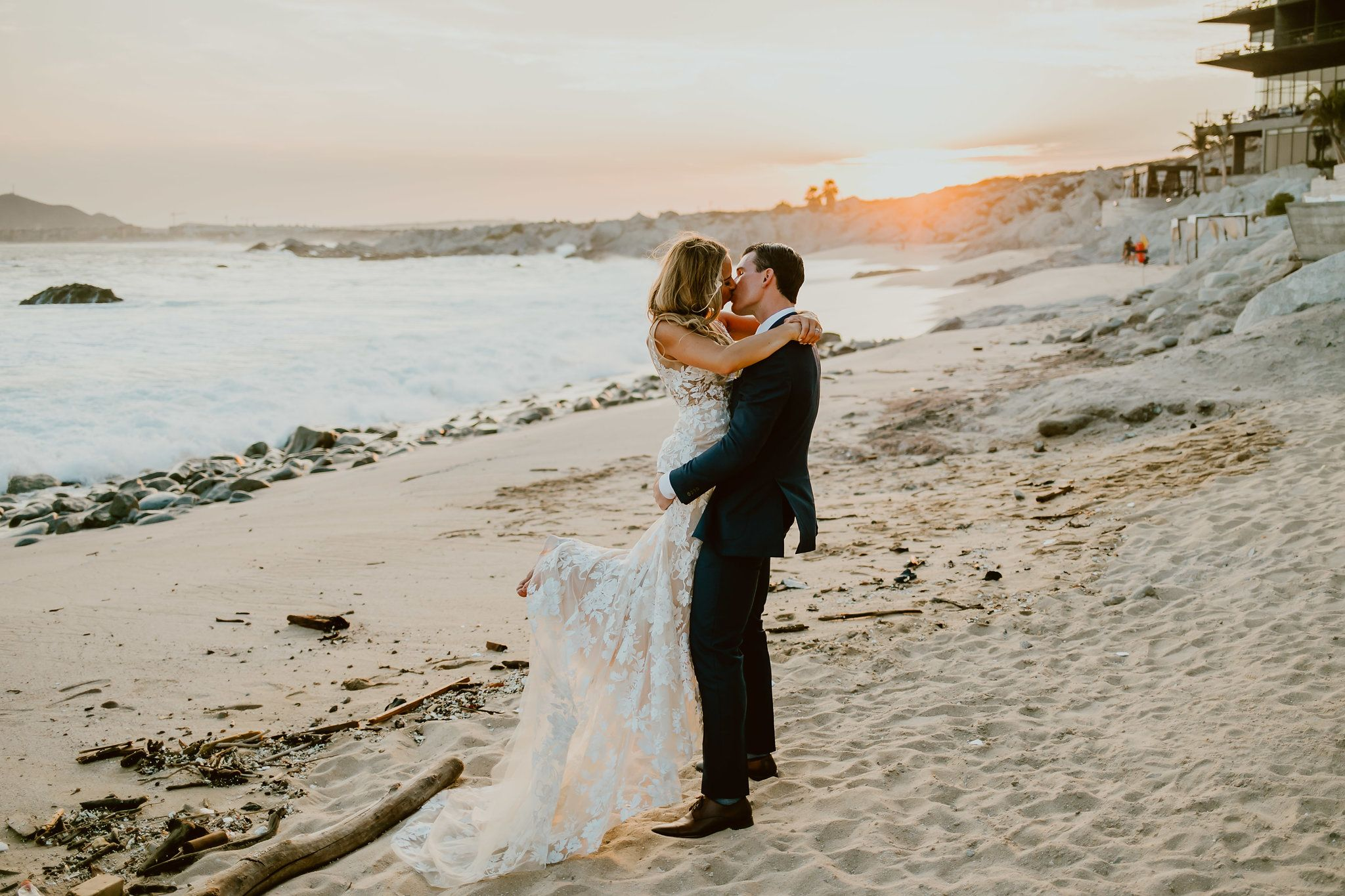 Bride and Groom kissing during photo session in Cabo San Lucas Mexico right in front of the Cape by Thompson Hotels. Wedding Planning by Cabo Wedding Services