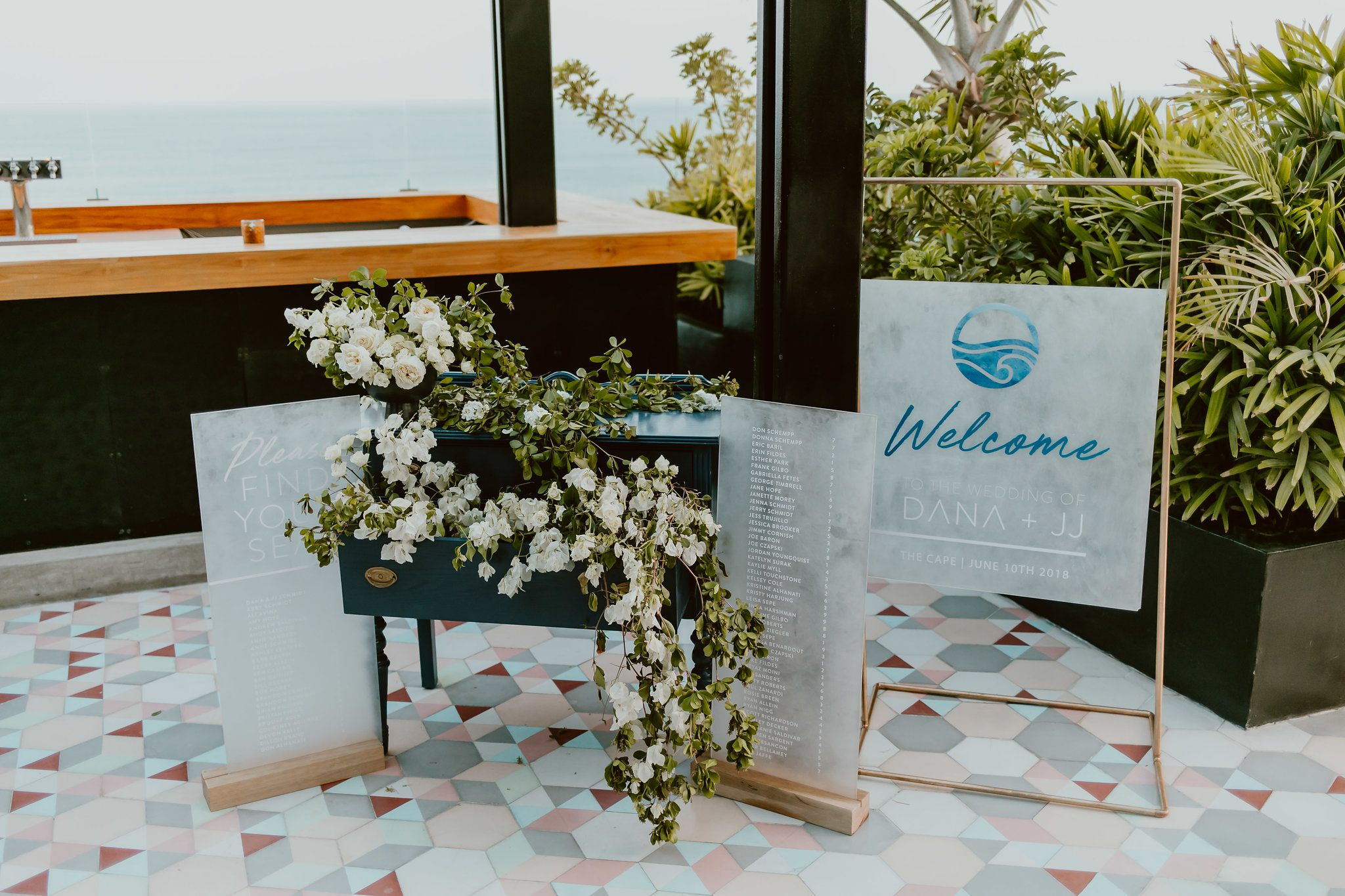 Welcome Table at the Rooftop at the Cape by Thompson Hotels. Details of Escort Table and Welcome sign by bells and whistles in Los Cabos Mexico. Wedding Planning by Cabo Wedding Services