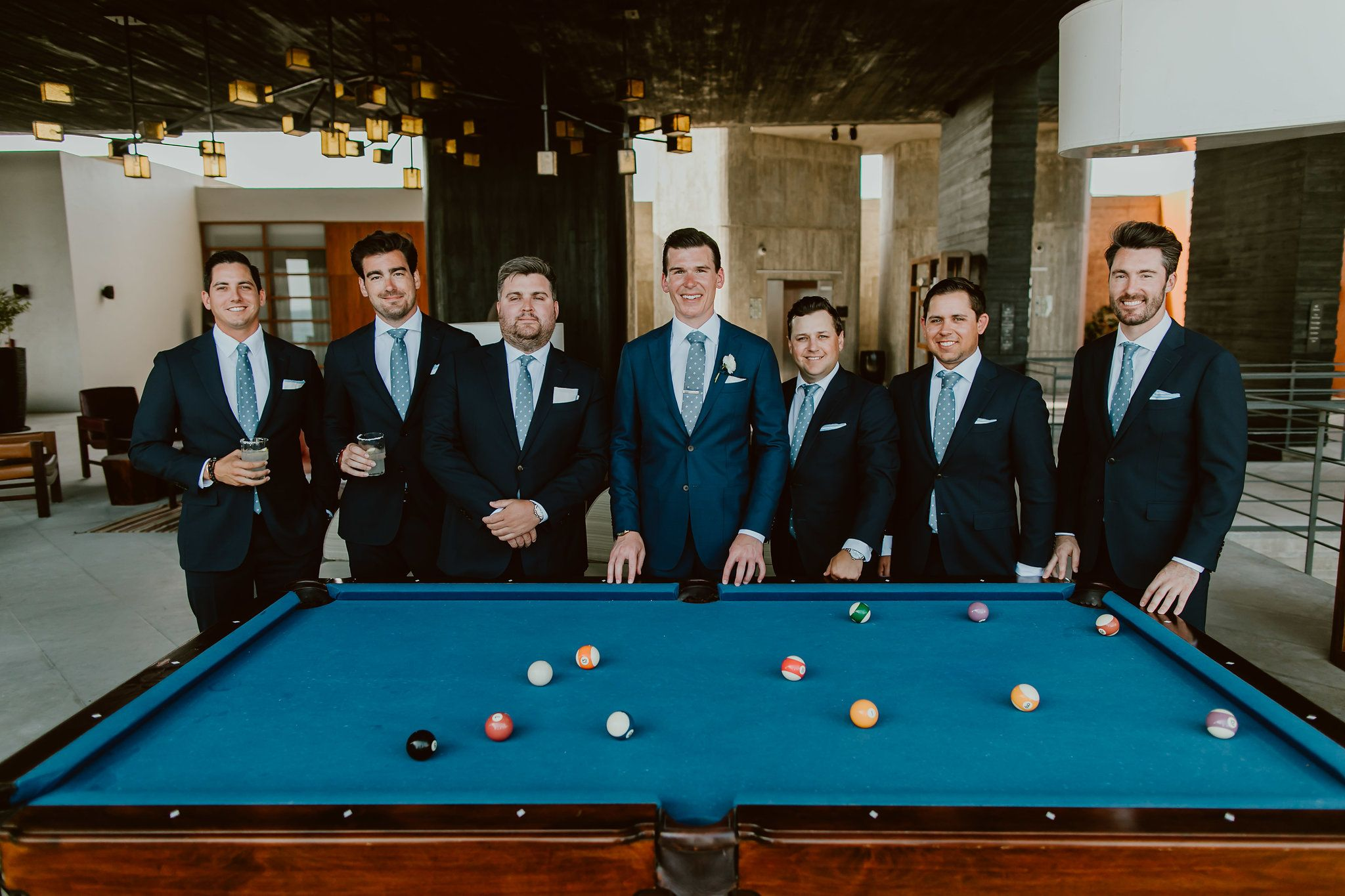 Groom and Groomsmen posing by the Pool Table at the Lobby bar at The Cape in Cabo San Lucas, Mexico. Wedding planning and design by Cabo Wedding Services