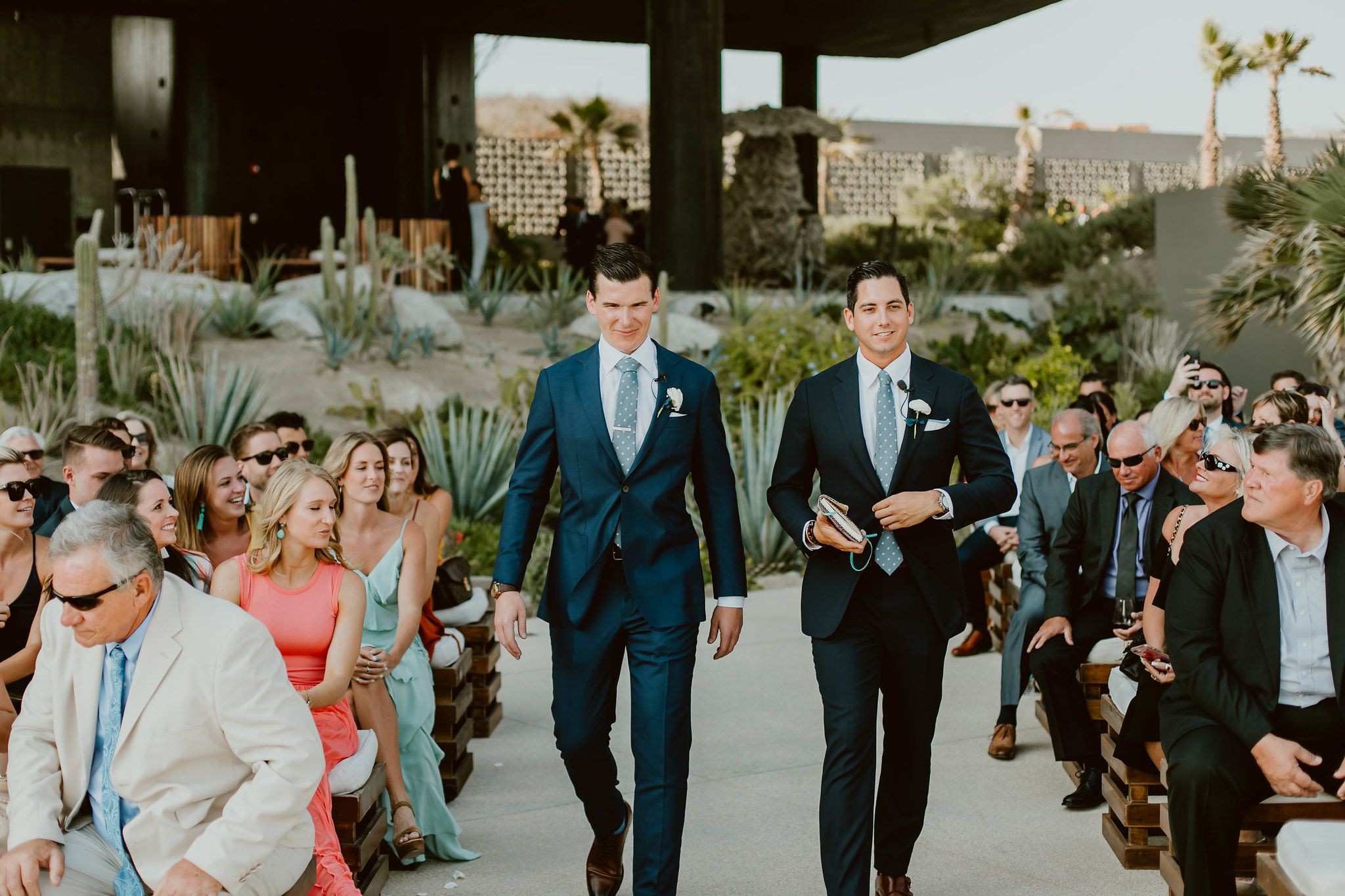 Groom walking down with the officiant during the Ceremony Processional. This photo was taken by Ana and Jerome at The Cape by Thompson Hotels in Los Cabos, Mexico. Wedding Planning by Cabo Wedding Services