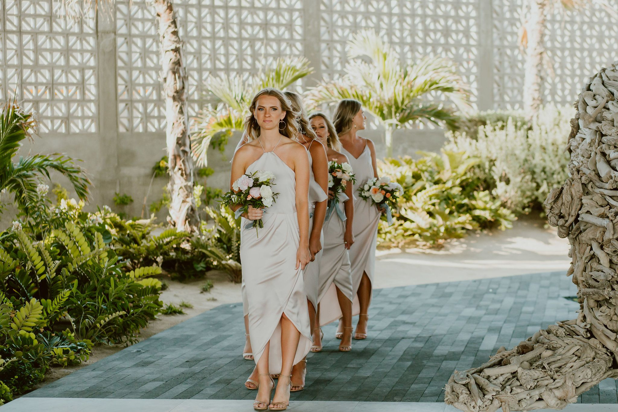 Bridesmaids walking down the aisle with their beautiful bouquets designed by Lola from Florenta Design. Photo was taken by Ana and Jerome Photography at The Cape Los Cabos, by Thompson Hotels