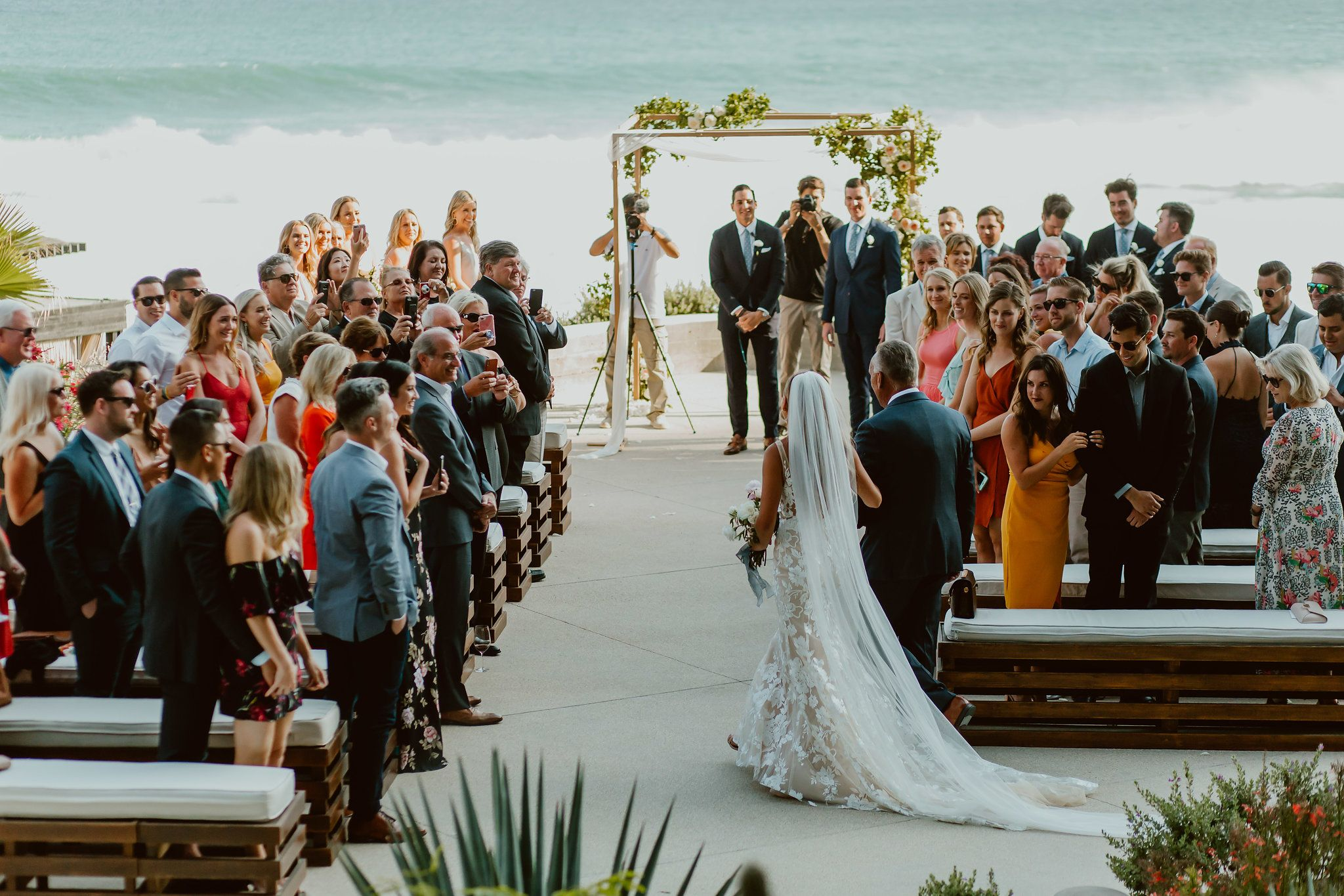 Bride walking on her way down to her groom with the Sea of Cortez in the backgroun. Photo taken by Ana and Jerome photography at The Cape by Thompson Hotels in Cabo San Lucas Mexico