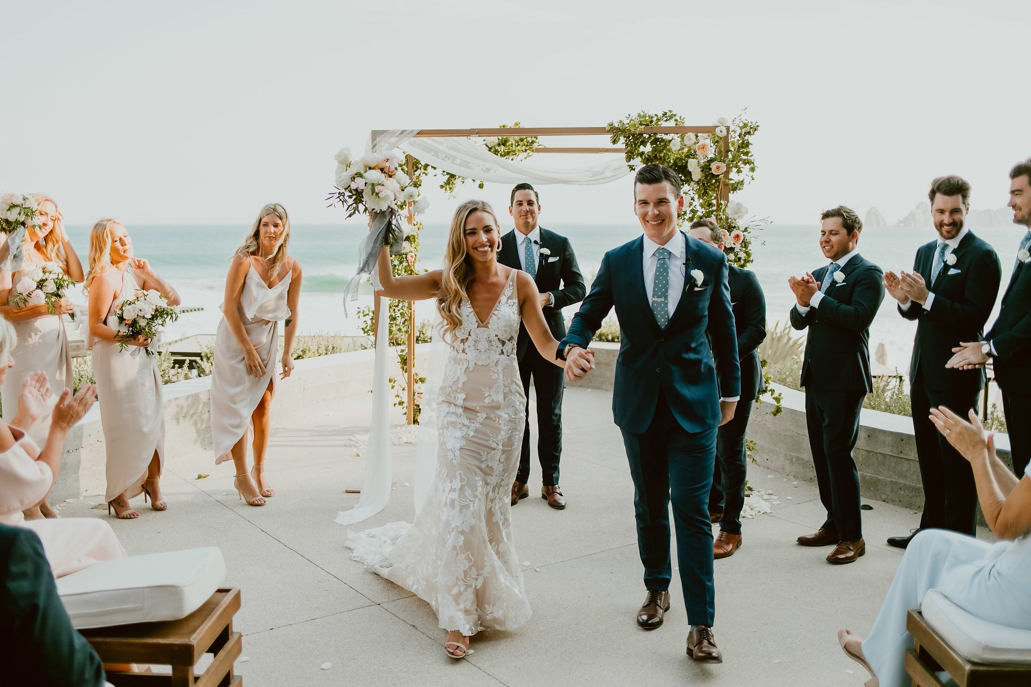 Bride and Groom recessional after their ceremony at The Cape Terrace in Los Cabos. Beautiful Dress made by Made with Love Bridal. Perfect design for a perfect bride! Wedding Planning by Cabo Wedding Services