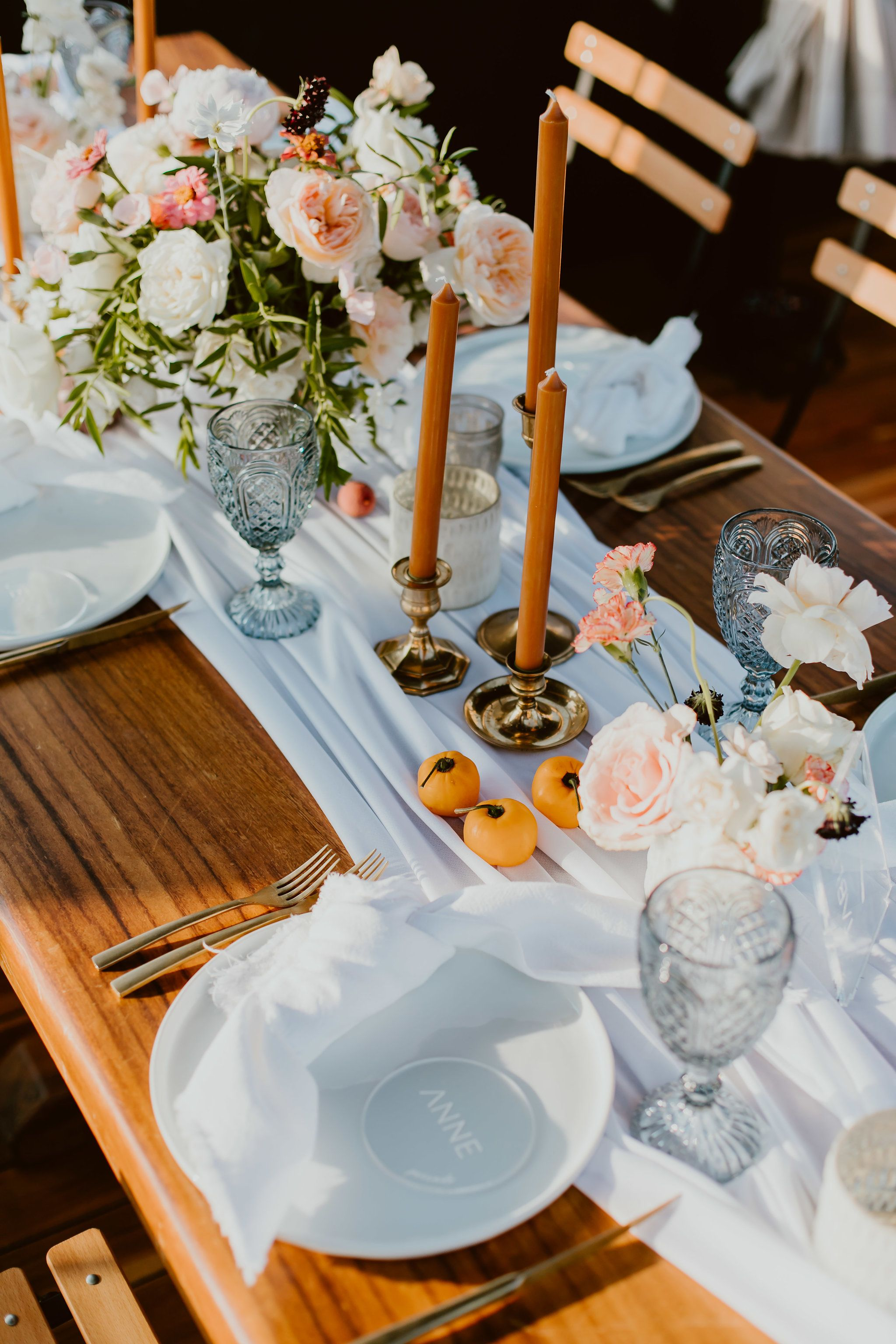 Beautiful table setup with white chargers, white napkins and beautiful table runners. There were brown candle sticks to match the papayas and beautiful wood tables to match. Candles and Flower centerpieces throughout the tables made it look full but still clean.