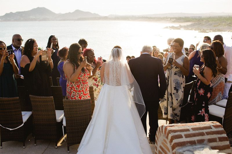Bride walking down to her wedding ceremony at Wedding Venue Sunset da Mona Lisa in Cabo San Lucas, Mexico. Wedding Planning and design by Cabo Wedding Services