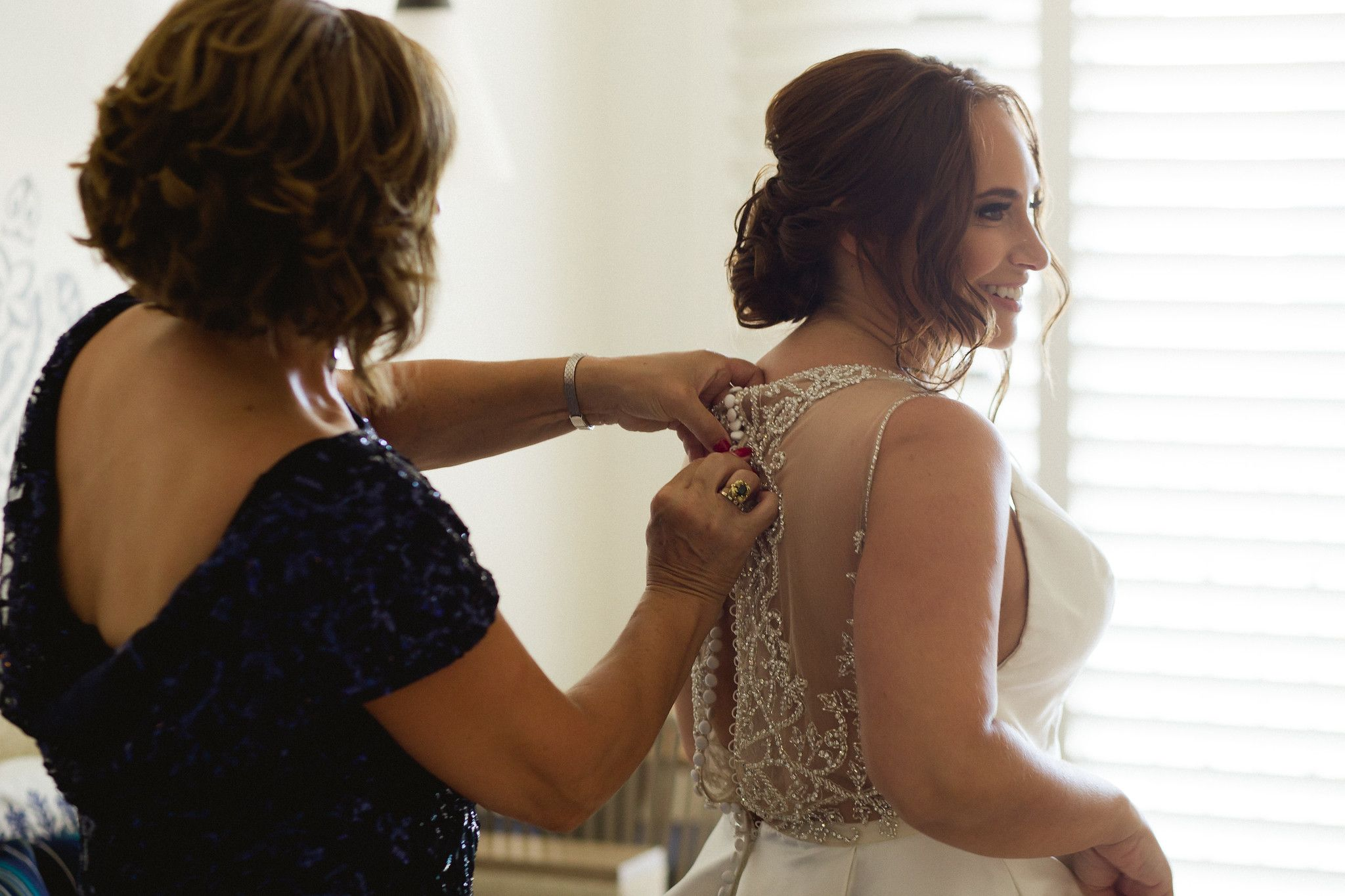 Bride on her wedding day getting ready and putting her dress on. She was staying at Hilton Los Cabos and that is where she got ready and Alma Vallejo with Cabo Makeup did her Hairstyle and Makeup. Cabo Wedding Services did their Wedding Planning and design