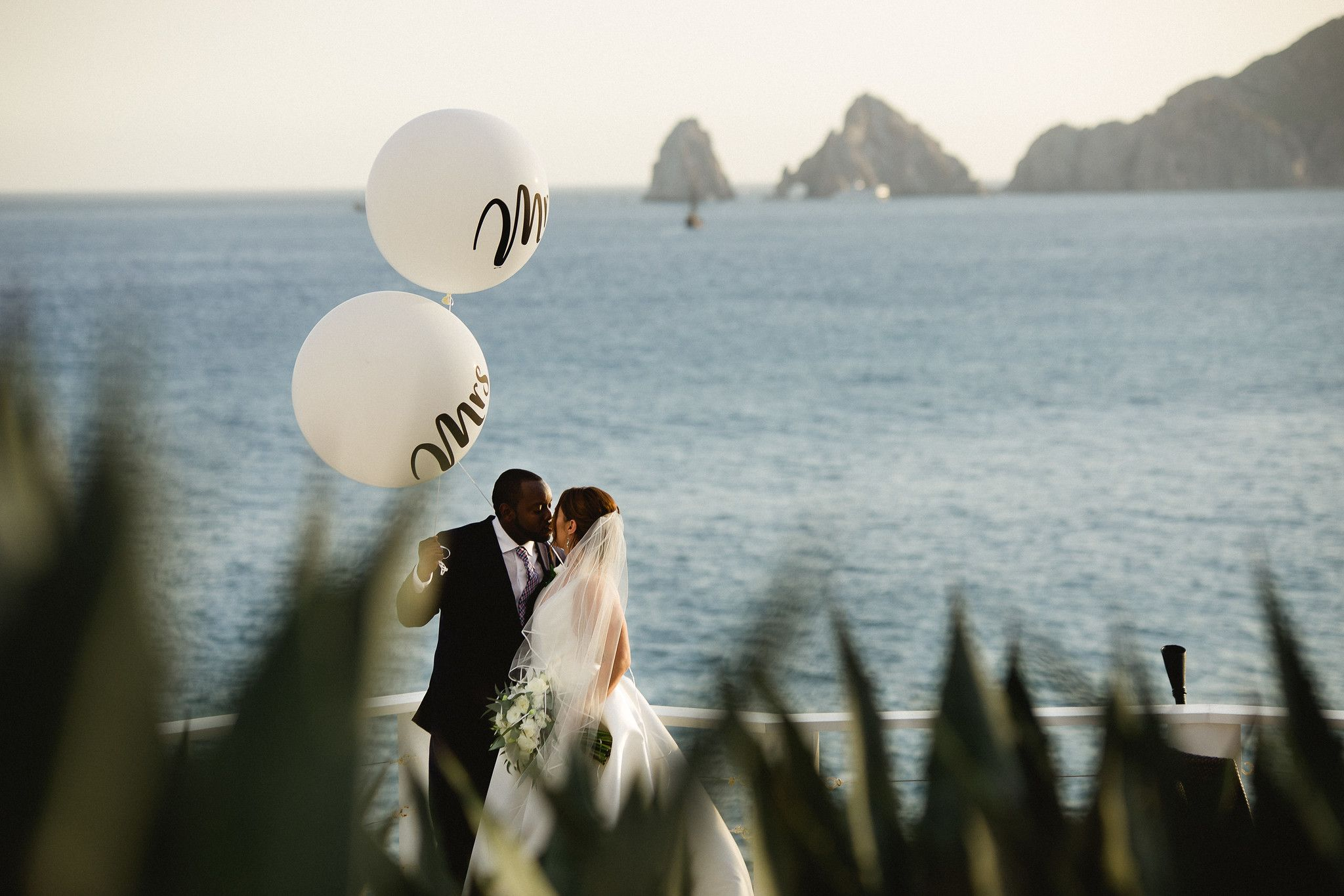 Bride and groom over looking the Sea of Cortez and the Arch in Los Cabos Mexico on their wedding day at Sunset da Mona Lisa located in Cabo San Lucas. Wedding Planning and design by Cabo Wedding Services