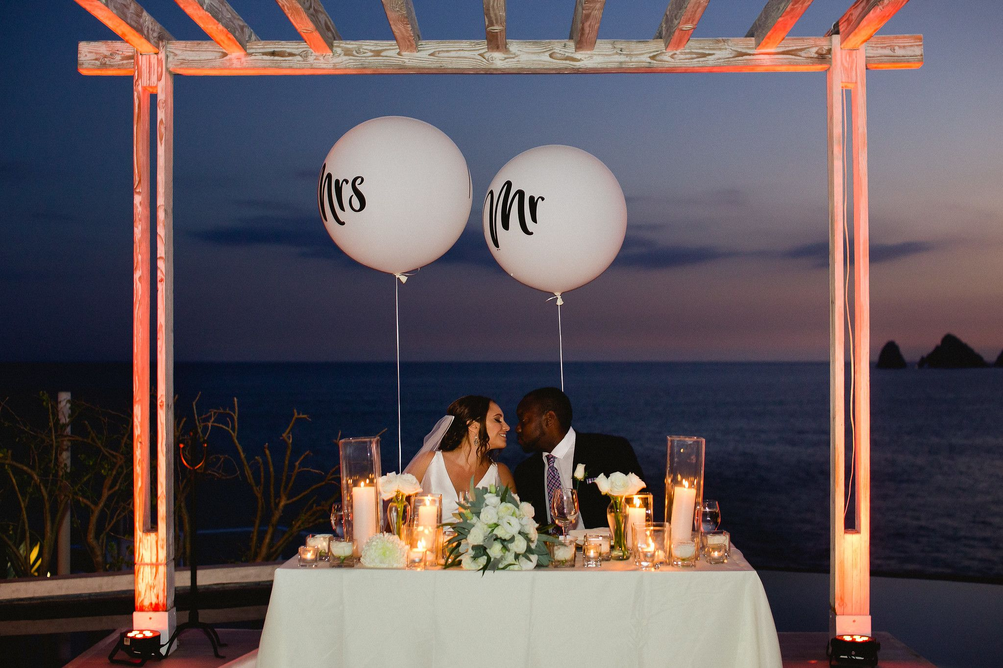 Bride and Groom at their sweetheart table at famous wedding venue in Cabo San Lucas, Mexico. Wedding planning and design by Cabo Wedding Services
