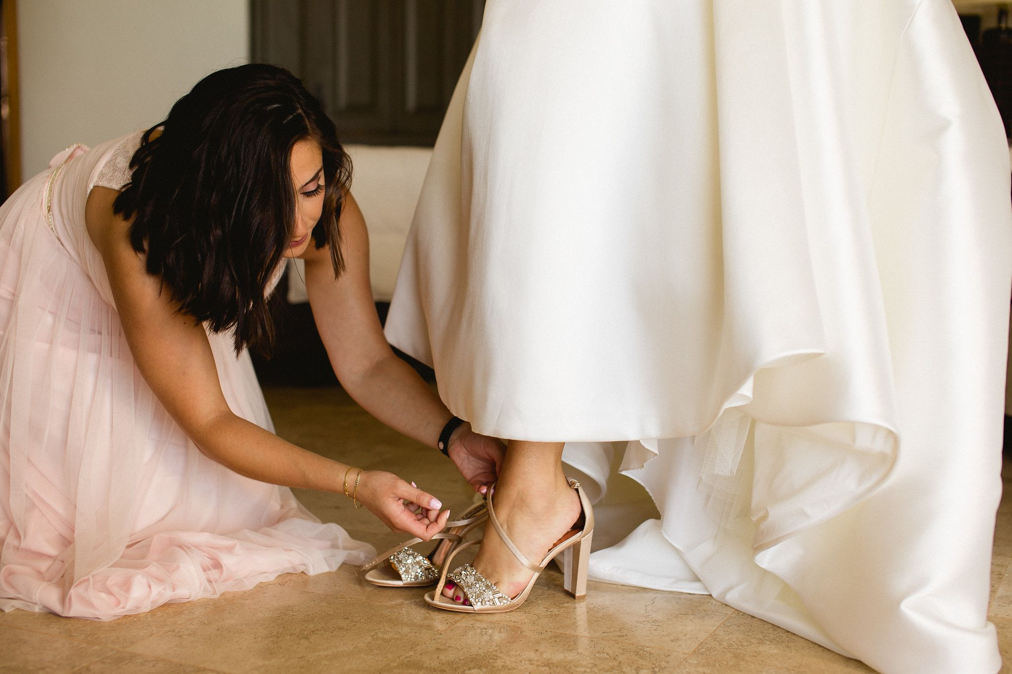 Maid of Honor helping the Bride to get ready and put her shoes on. She got ready at Hilton Los Cabos with all of her family and friends in Cabo San Lucas Mexico, with Cabo Wedding Services helping her plan and design her wedding day