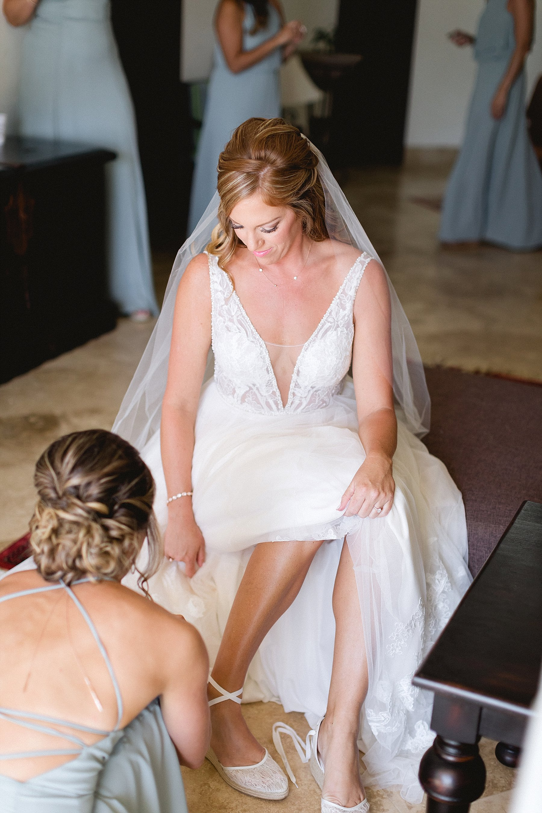 Maid of Honor helping Bride put her shoes on at her Wedding Day. They were getting ready at Hacienda Encantada in Cabo San Lucas, Mexico, and theiir wedding was at Flora Farms. Wedding PLanning by Cabo Wedding Services and Photography by Sara Richardson