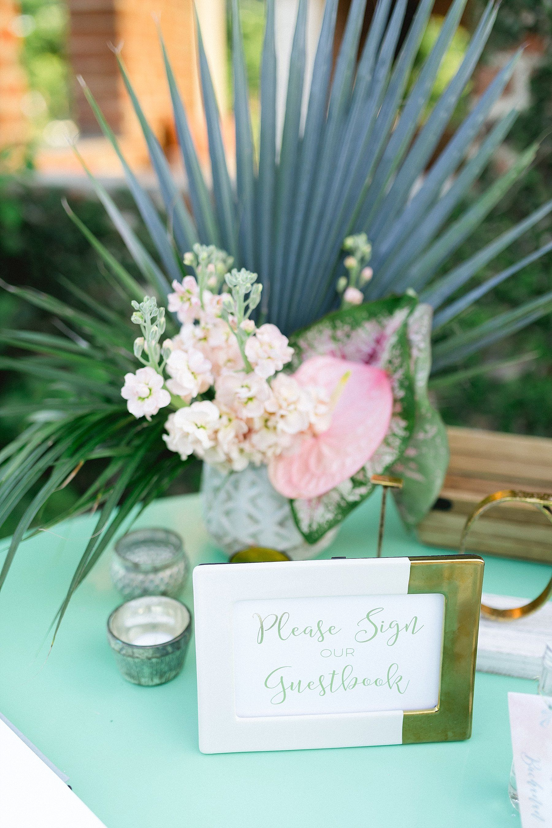 Guest signing book table with a floral arrangement. The Wedding took place at Flora Farms in Los Cabos, Mexico. Wedding Planning by Cabo Wedding Services. Photography by Sara Richardson