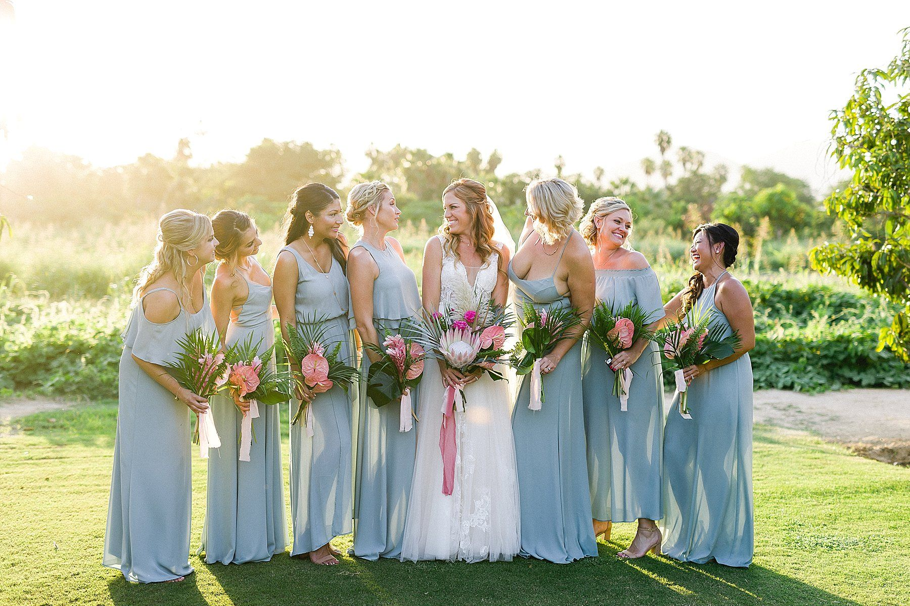 Bride with Bridesmaids posing at wedding venue Flora Farms in Los Cabos, Mexico. Wedding Planning by Cabo Wedding Services and Wedding Photography by Sara Richardson