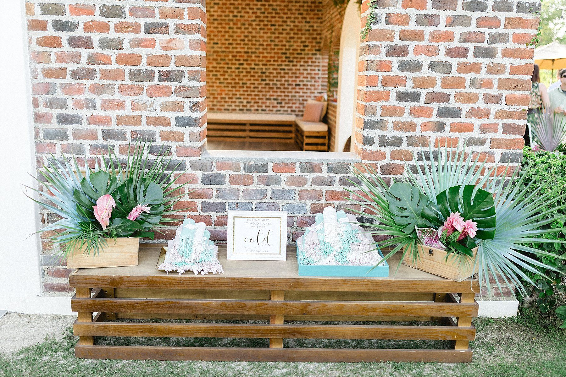 Pashmina setup with flower arrangements on bench. Great to do when the weather can be a bit chilly and works great for wedding favors. Wedding Planning by Cabo Wedding Services and Wedding Photography done by Sara Richardson