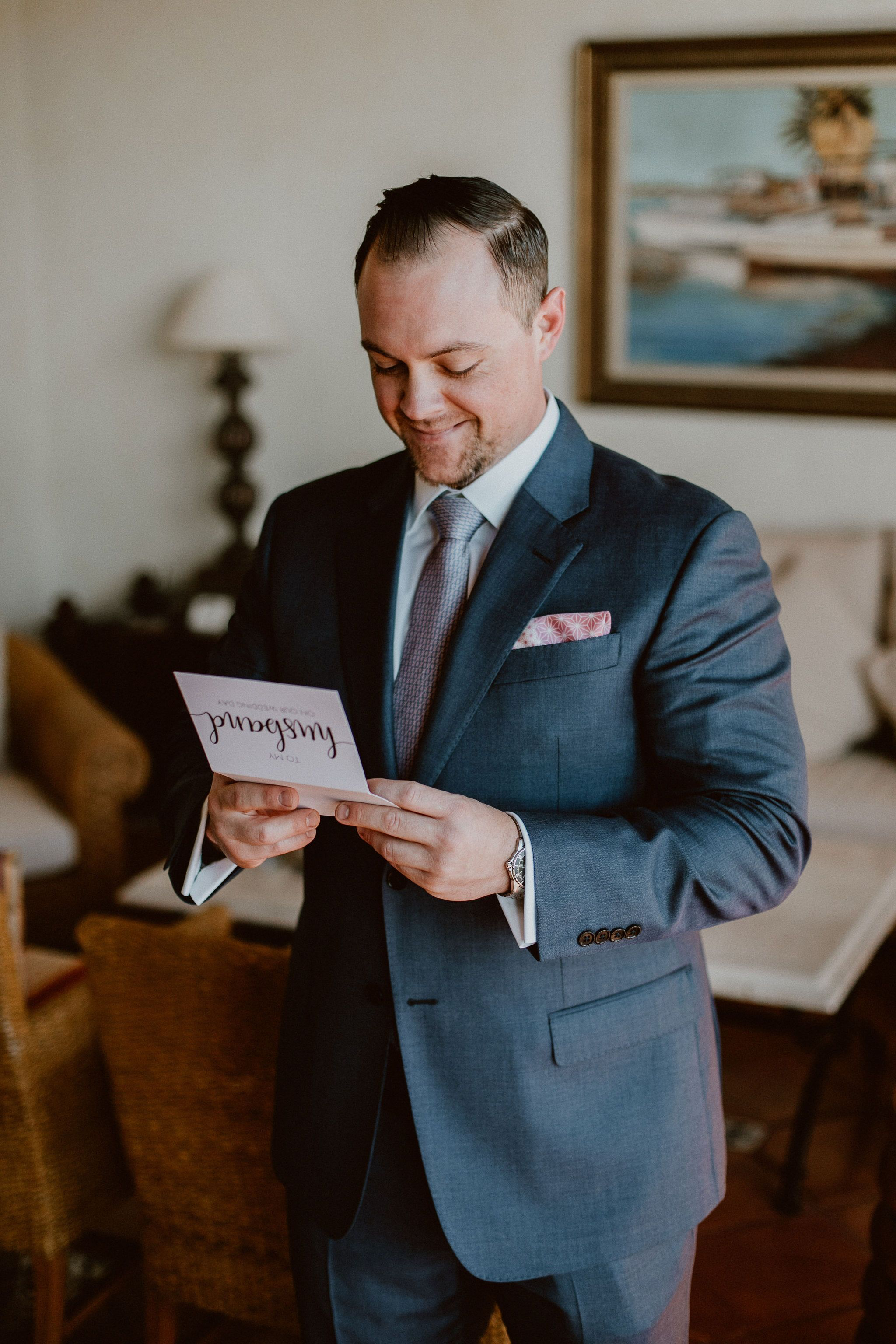 Groom reading the card his bride wrote to him right before the Wedding Ceremony on their wedding day. Their wedding was at Cabo del Sol, and we, Cabo Wedding Services were there Wedding Planners. They hired Ana and Jerome for their photography, and Emporio Floral Art for their Flowers.