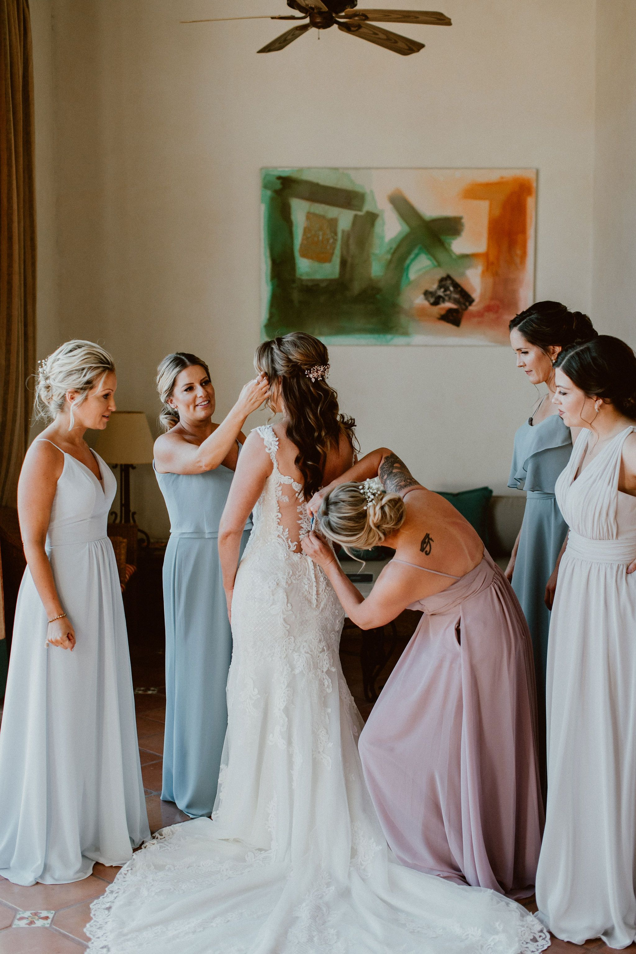 Bride getting ready with her Bridesmaids, getting her dress on. This was at her Bridal Suite in Cabo Del Sol, in Los Cabos, Mexico. This was January, 2019 and she hosted her wedding day with 50 of her closest Family and Friends, who most of them came from Oregon and Minnesota.