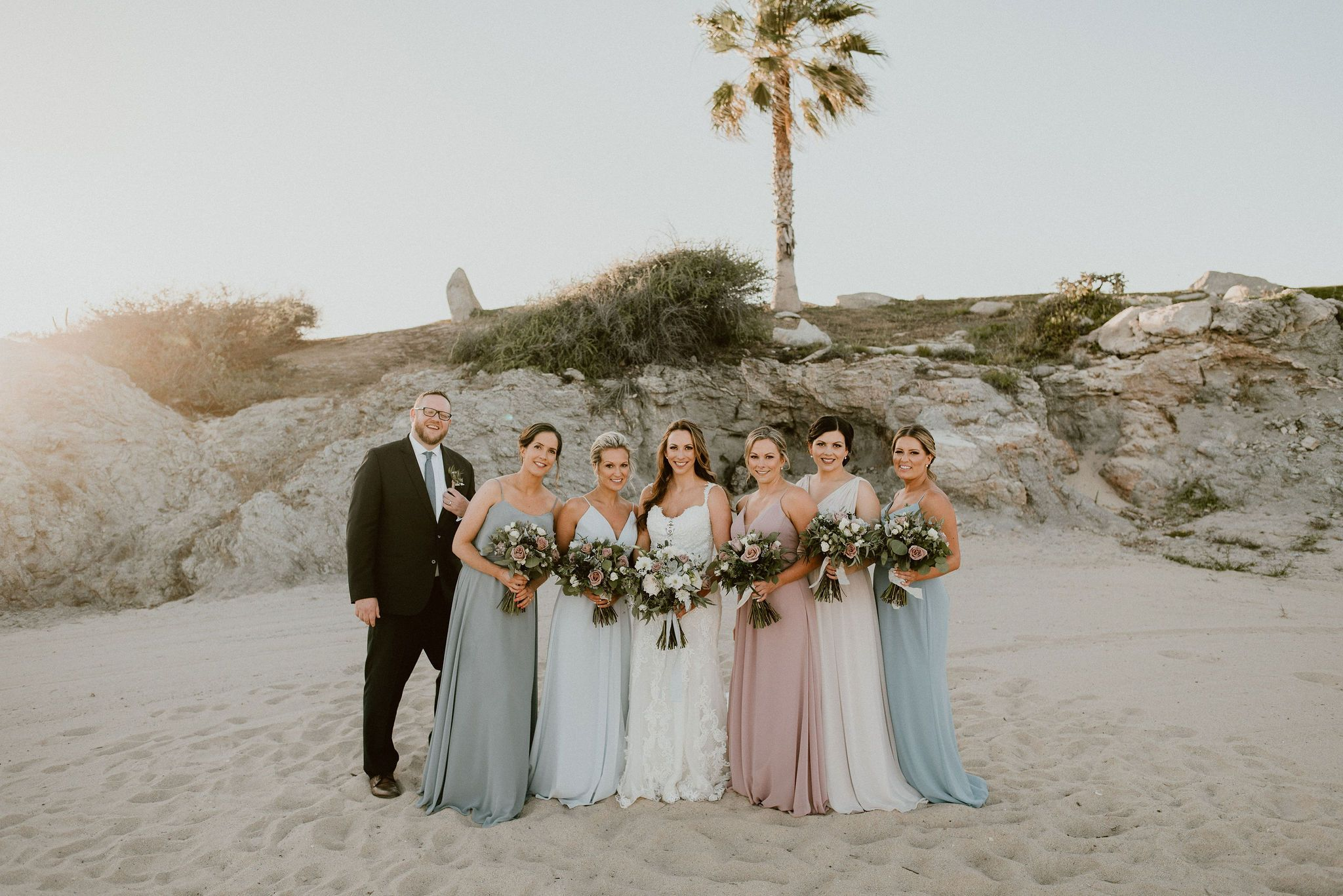 Bride with Bridesmaids at the Beach taking their Bridal Portraits with the Bridal Party. This was at Cabo del Sol in Cabo San Lucas, Mexico. Wedding Planning was done by Cabo Wedding Services.