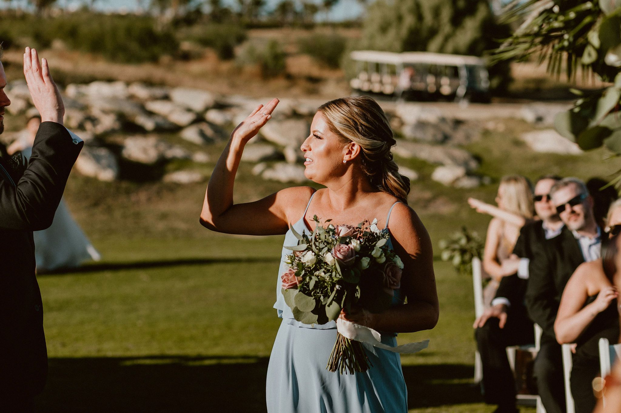Bridesmaid high fiving guest during the Ceremony Processional. This wedding was at the Cabo Del Sol golf Course, in Los cabos Mexico. Wedding Planning by Cabo Wedding Services. The Photographers were Ana and Jerome. They had Emporio Floral Art for flowers and Jesse Wolff as their designer in Rentals + Decor.