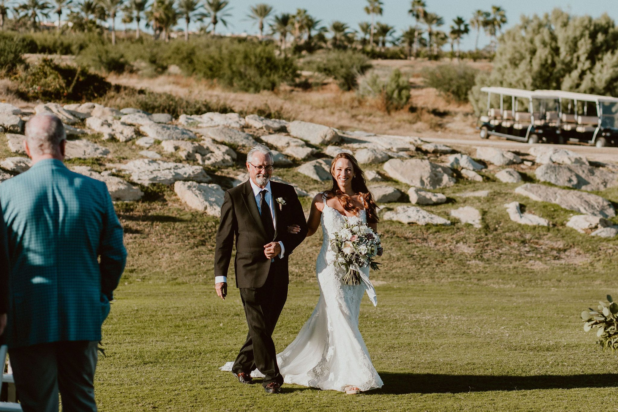 Bride with her dad walking down the Ceremony Aisle at Cabo del Sol Gold Club House. Her Wedding was in Cabo San Lucas, Mexico. Destination Wedding Planning by Cabo Wedding Services.