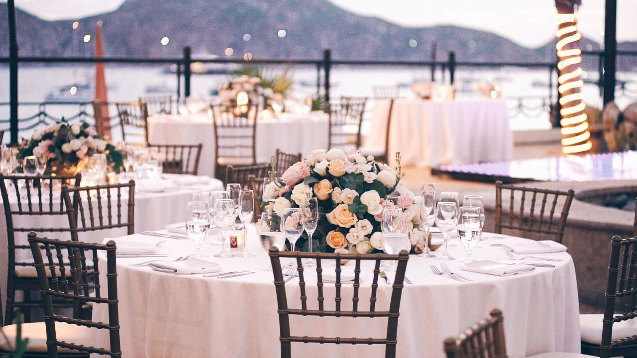 Table setup with flowers at Villa del Palmar in Los Cabos Mexico. The Wedding Reception took place at the Desert Terrace at the Villa Group in Los Cabos Mexico. Overlooking the Ocean, the Bride and Groom were able to have dinner with all of their close loved ones looking over the beautiful Medano Beach