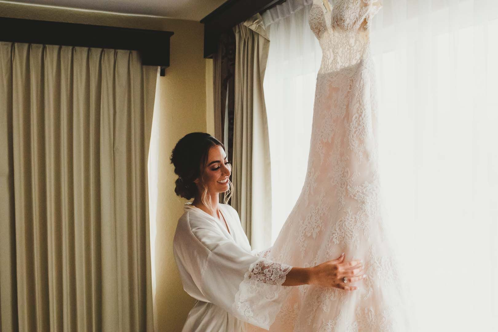 Bride holding her Wedding dress at the hotel. She stayed at Villa del Palmar in Los Cabos, Mexico.
