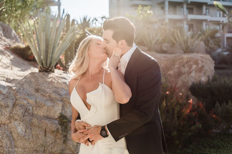 Bride and Groom kissing at The Cape by Thompson Hotels in Los Cabos, Mexico. Wedding Planning by Cabo Wedding Services.