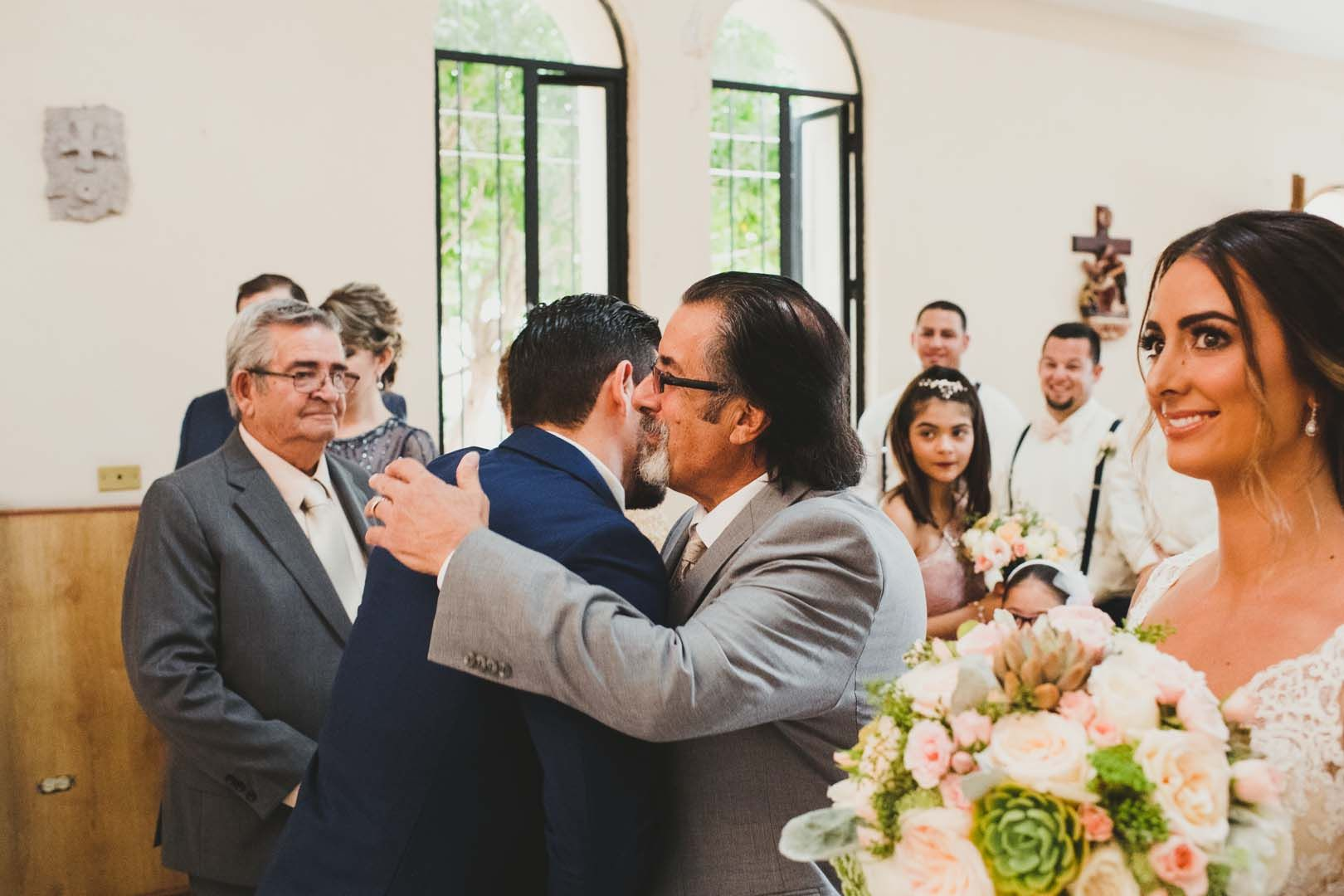 The father of the Bride is hugging the Groom as he hands his daughter off. This wedding was at the Evangelist Church in Los Cabos Mexico.