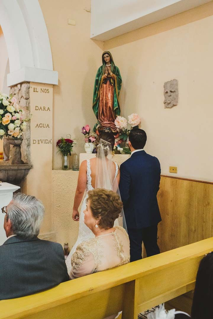Bride and Groom in front of the Virgin Mary at their Wedding that took place in the Evangelista church in Cabo San Lucas Mexico. One of the oldest churches of the Region, it has seen many marriages throughout the years