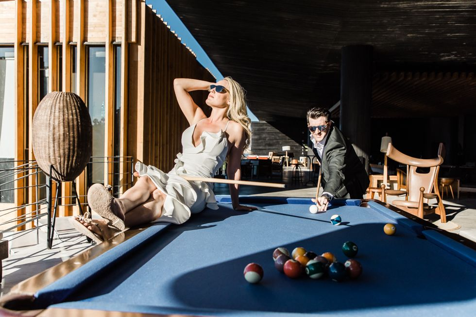 Bride and Groom posing by the pool table at The Cape by Thompson Hotels in Los Cabos Mexico. They had a great photo session with Photographer Daniel Jireh