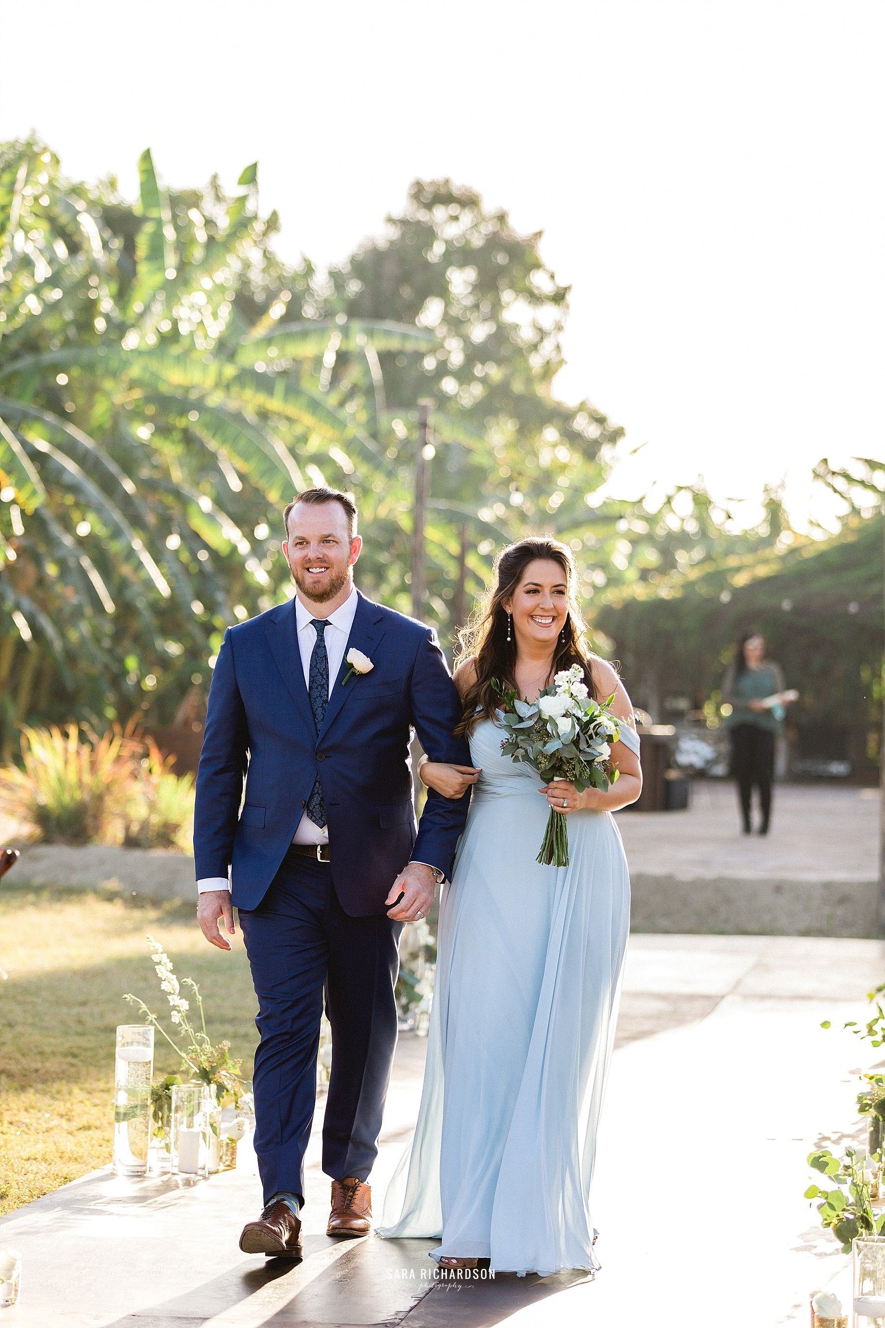 Bridesmaid and Groomsman walking down the aisle, making way for the beautiful Bride. This wedding took place in February of 2019, in Los Cabos Mexico. It is one of the biggest wedding destinations in the world.