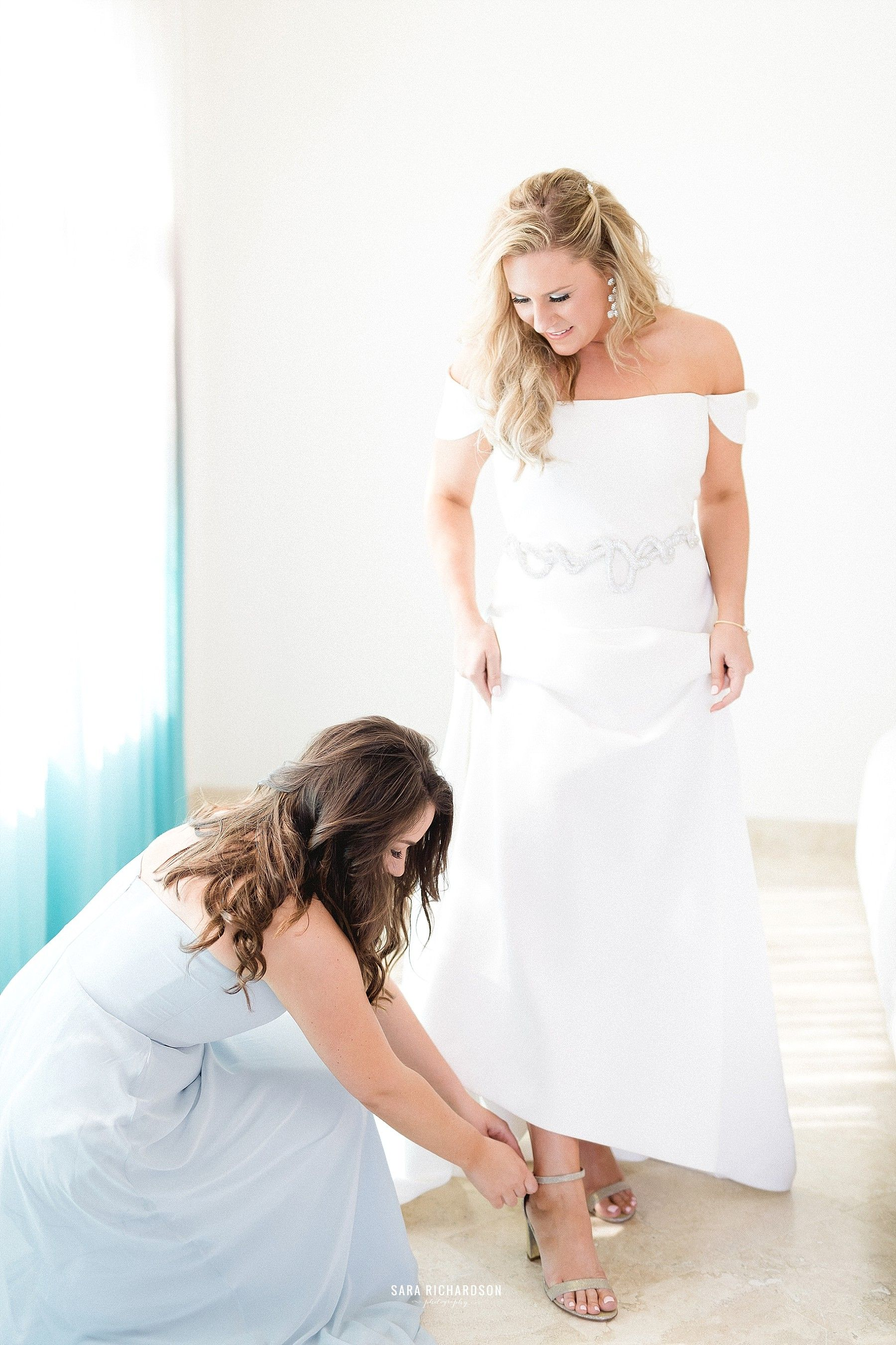 Brides sister helping her put her shoes on. The Bride, Lindsey, decided to go with Jimmy Choo shoes, which are always the perfect shoes to wear on your Wedding Day.