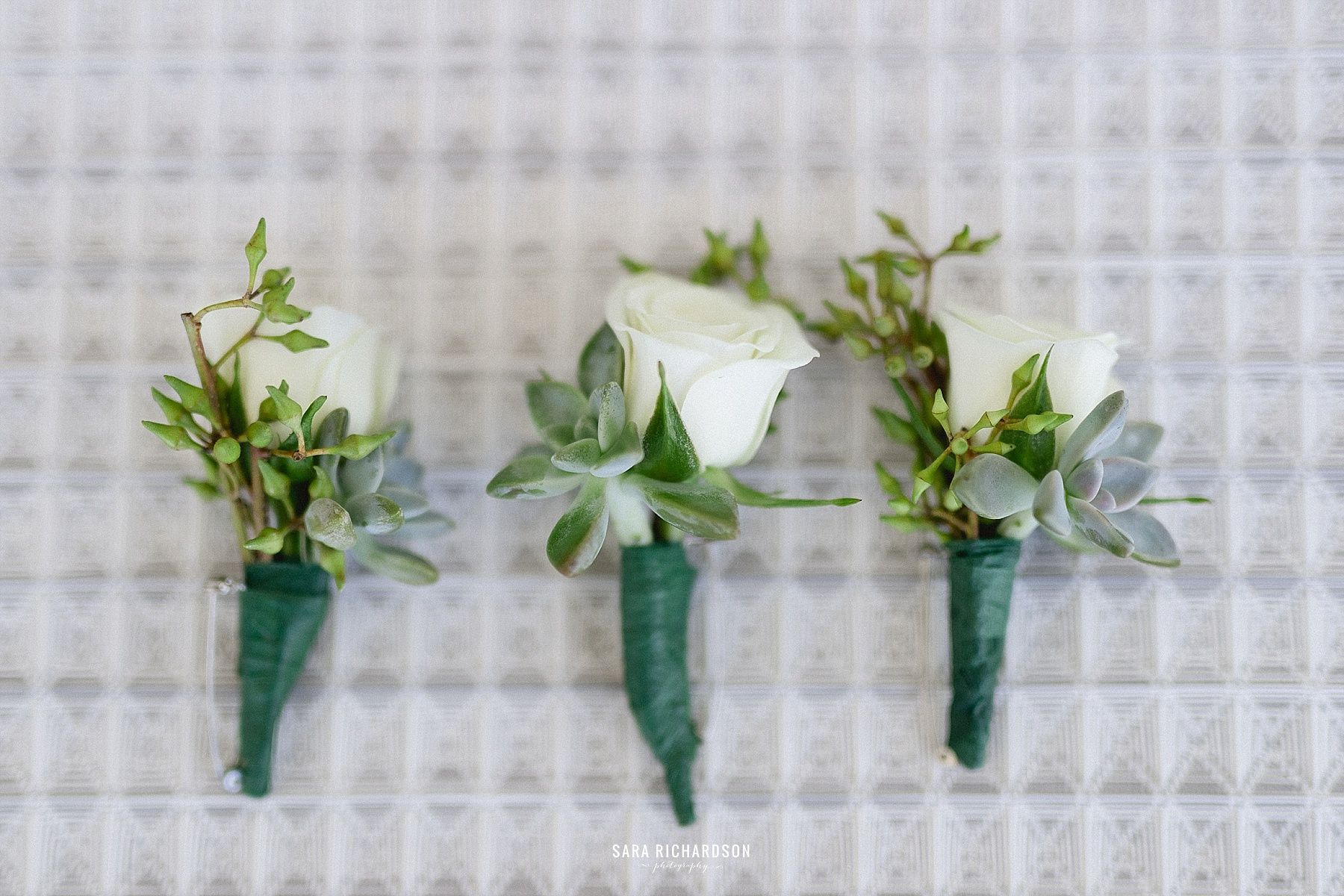 Perfectly cut mini roses for the Groom's Boutonniere. He looked so stunning with the white contrast and the blue in his suit. He looked flawless. Photography was done by Sara Richardson.