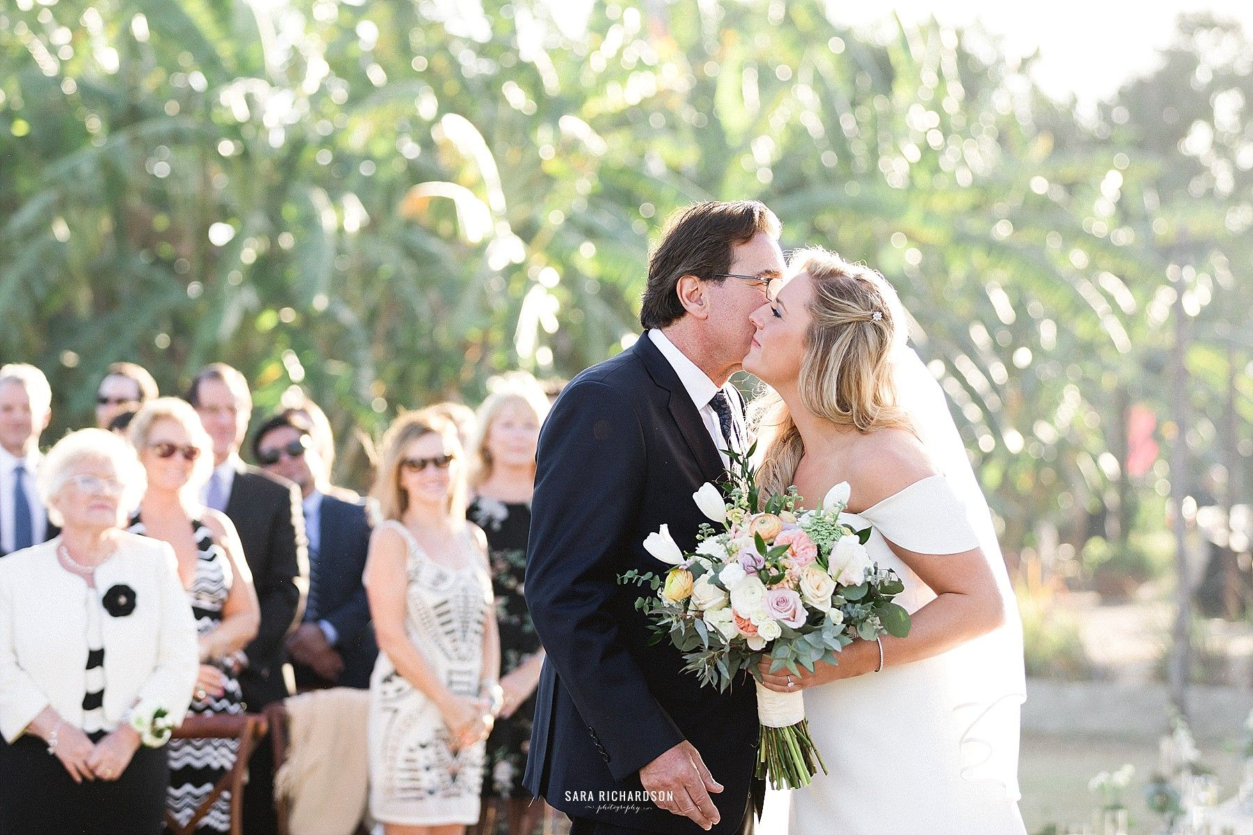 Bride kissing her dad as he hands her off prior to the ceremony beginning.
