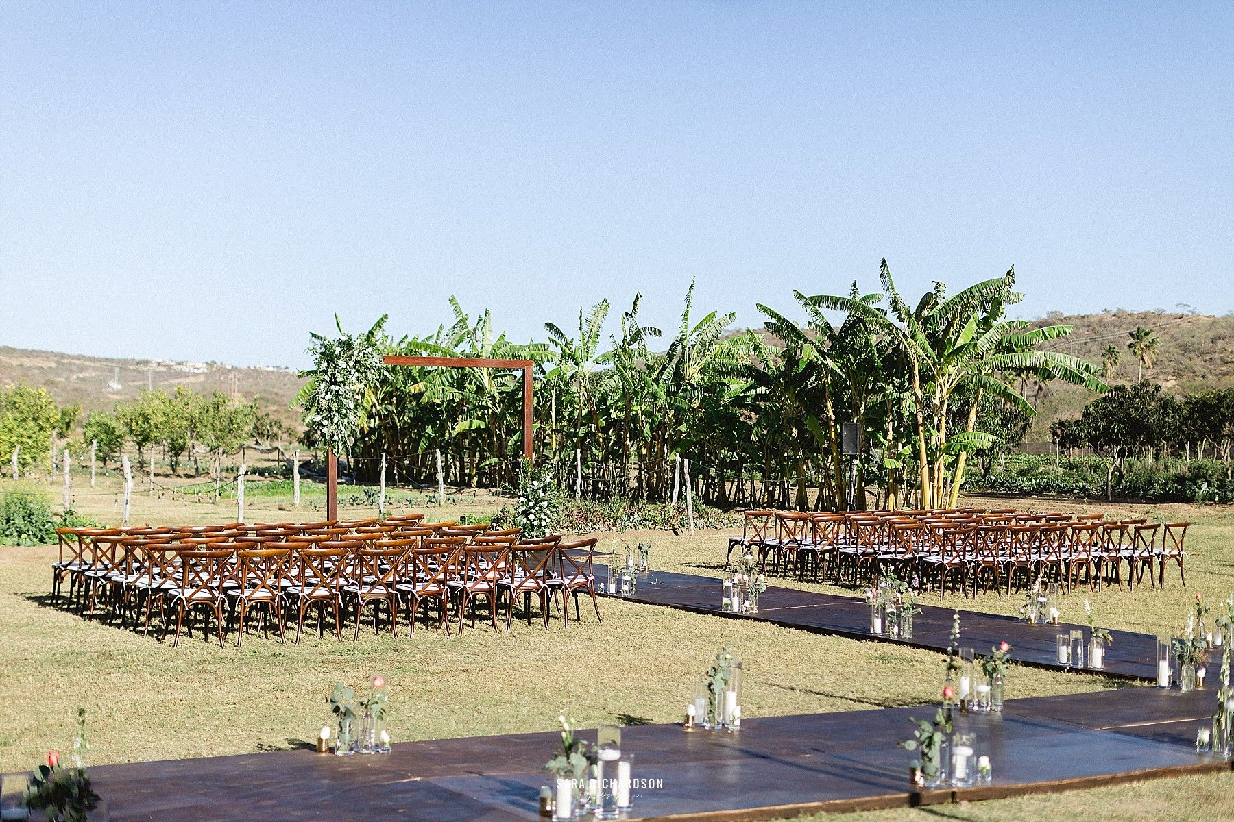 This is the Ceremony setting for Lindsey and Noel's Wedding. They decided to have a hard wooden floor for their guests so they do not have to walk in the grass, since most of them wore heels. We decided to decorate the aisle and make it look a little fuller.
