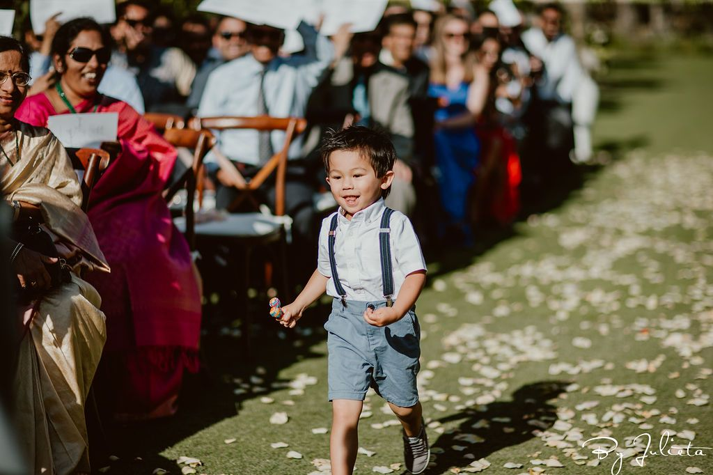 Ring Bearer running down the aisle at Wedding Venue Flora Farms in Los Cabos Mexico. Cabo Wedding Services did the Wedding Planning and Julieta Amezcua was the Photographer.