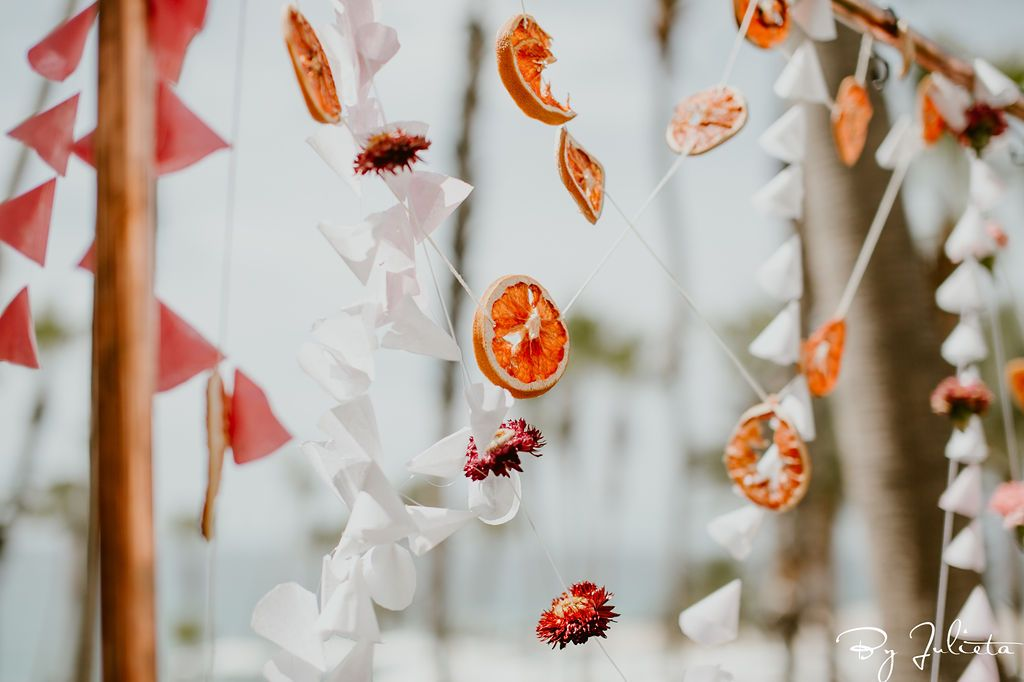 Haldi Backdrop designed by Cabo Wedding Services. It was dried oranges, flowers and beautiful garlands. Haldi ceremony took place at the Hilton Los Cabos, and the wedding planning was done by Cabo Wedding Services.