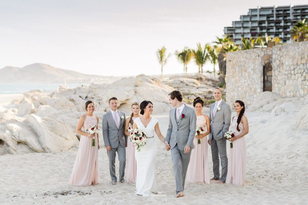 Bride and groom enjoying time with their bridal party on the beach in Los Cabos Mexico, at their Destination wedding at Villa las Rocas