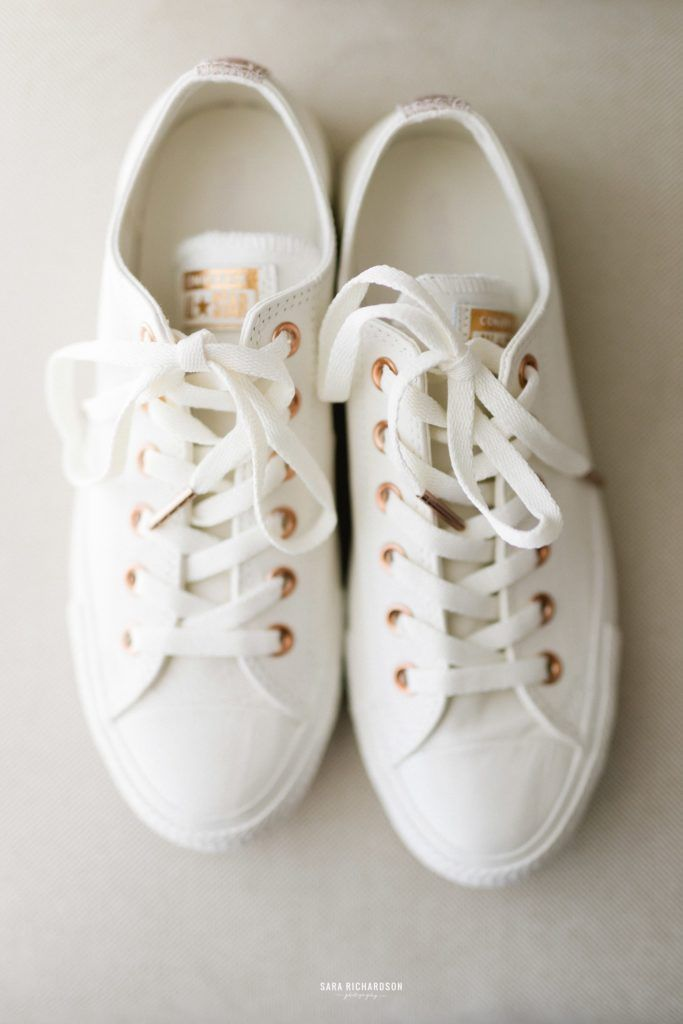 Brides wedding shoes. She wanted to go comfortable in Converse Tennis Shoes and got the cutest white ones with gold touches.