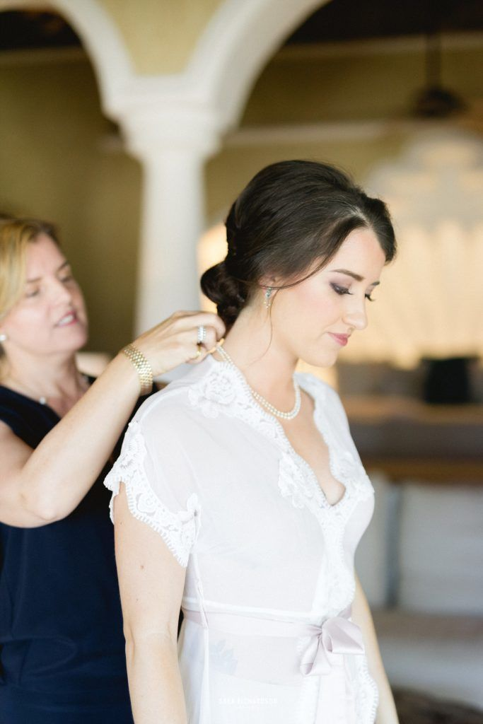 Bride getting ready with her mom at the villa she rented for her wedding weekend in Los Cabos Mexico. She had Sara Richardson as her photographer and Cabo Wedding Services as her wedding Planners. She wore a beautiful lose dress with Gucci perfume.