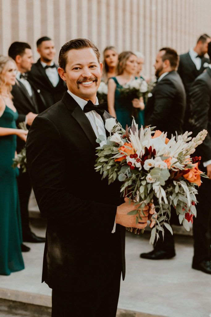 Groom standing at his Wedding Venue, Acre Baja with the Bridal Bouquet. He looked stunning, even with flowers!