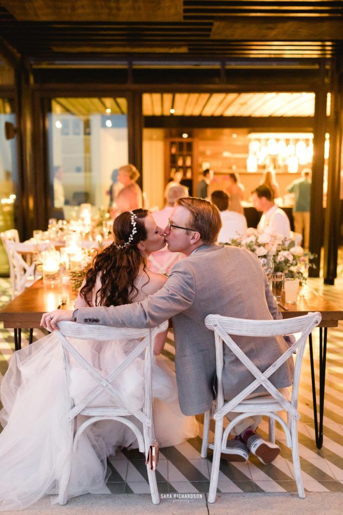 Bride and Groom kissing at their Sweetheart Table as Guests aligned their glasses with their forks for the Bride and Groom to Kiss. This photo was taken by Sara Richardson at The Cape in Los Cabos Mexico