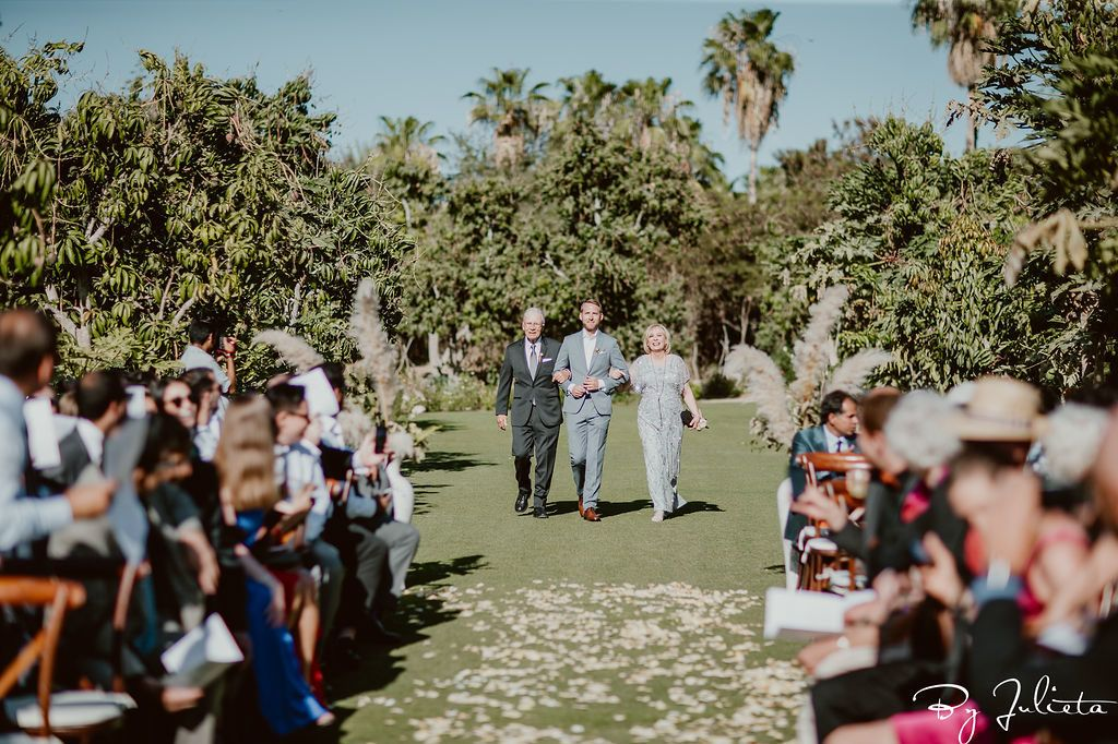Groom walking down to the ceremony at his wedding venue at Flora Farms in Los Cabos Mexico.