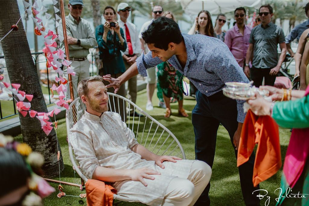 Guests came up to the Bride and Groom and put turmeric on them to cleanse. It was part of the Haldi ceremony at the Hilton Los Cabos.