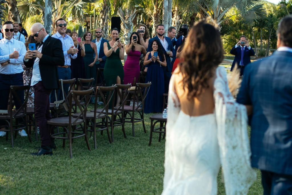 Bride walking down the aisle at her wedding venue in Los Cabos , Mexico, at Acre Baja.