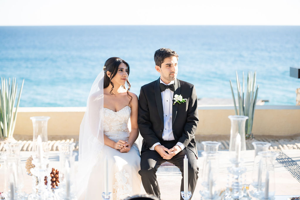 Bride and Groom sitting at their Sofreh on their wedding day in Los Cabos, Mexico. Wedding Planning was done by Jessica Wolff from Cabo Wedding Services.