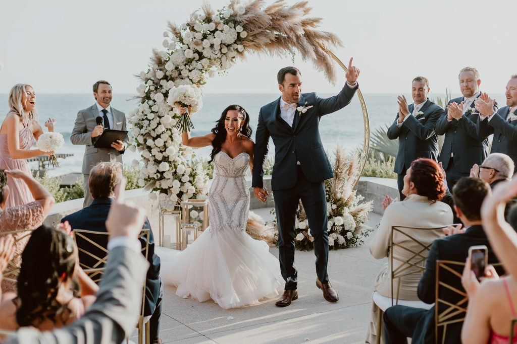 Bride and Groom doing the recessional, right after the ceremony when they were announced husband and wife, at The Cape in Los Cabos, Mexico. Wedding planning was done by Cabo Wedding Services